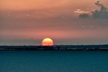 Red, Orange Sun Setting Over Gulf Of Mexico Waters, Land Foreground