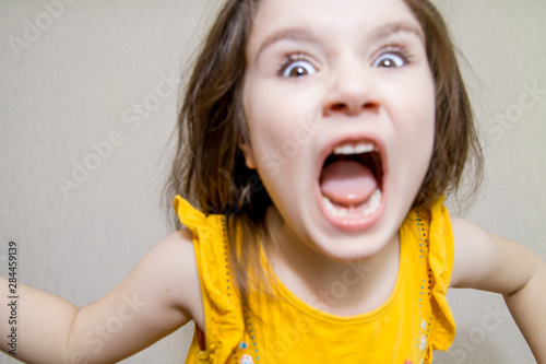 Fényképezés  defocused funny close up portrait of a Little agressive angry girl screaming on