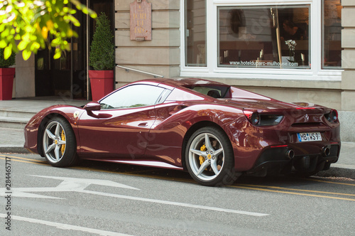 Photo red ferrari 488 parked in the street in front of luxury Hotel