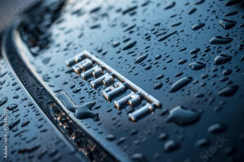 Valokuvatapetti closeup of rain drops on black ferrari logo