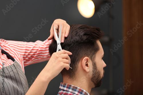 Photo Barber making stylish haircut with professional scissors in beauty salon, closeu