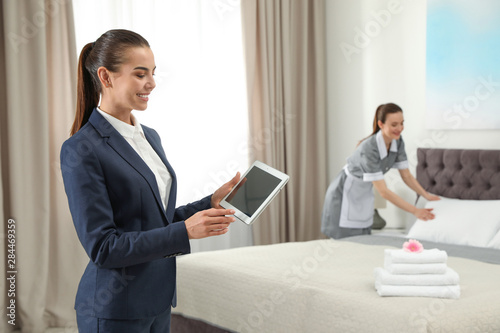 Fototapeta Housekeeping manager with tablet checking maid work in hotel room