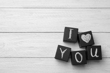 Black Cubes With Chalk Written Words I LOVE YOU On White Wooden Table, Flat Lay. Space For Text