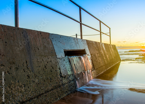Overflow water flowing out of an ocean beachside pool Poster Mural XXL