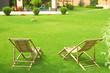 Leinwandbild Motiv Wooden deck chairs in beautiful garden on sunny day