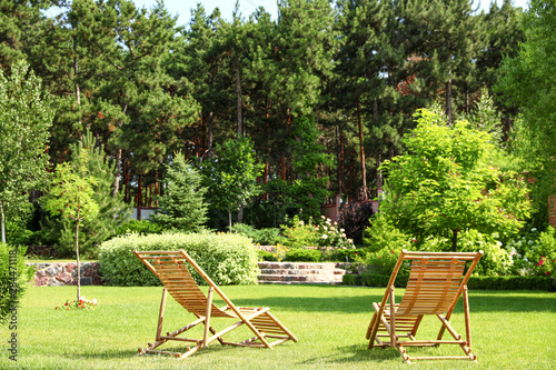 Fotografia  Wooden deck chairs in beautiful garden on sunny day