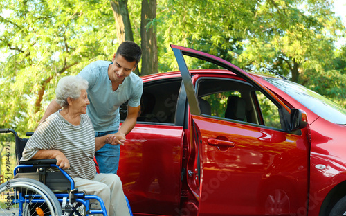 Pinturas sobre lienzo  Young man helping disabled senior woman in wheelchair to get into car outdoors