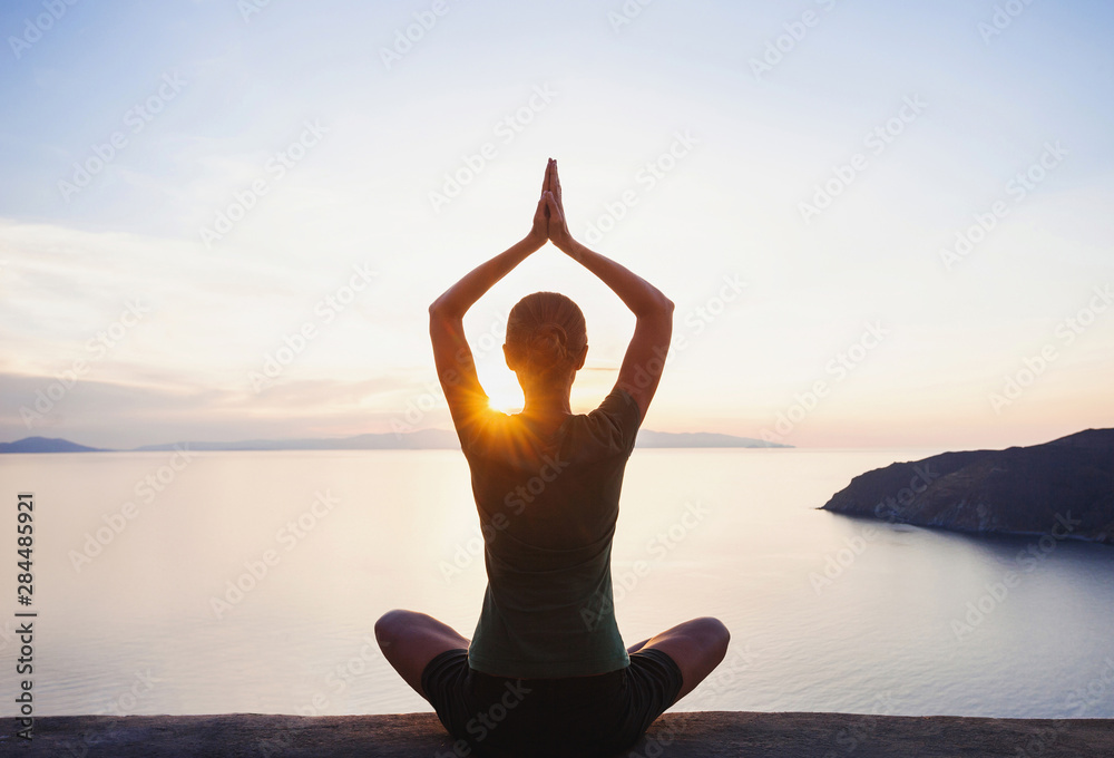 Fototapeta Young woman practicing yoga near the sea at sunset. Harmony, meditation  and travel concept. Healthy lifestyle