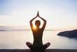 Leinwandbild Motiv Young woman practicing yoga near the sea at sunset. Harmony, meditation, healthy lifestyle, relaxation, yoga, self care, mindfulness concept