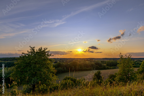 Photo Stands Sunset A beautiful sunset with a golden sunshine on a late summer evening. Concept: landscape or travel