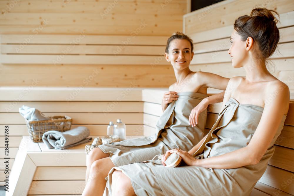 Fototapeta Two girlfriends relaxing in the sauna