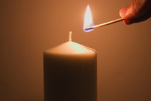 Lighting A Candle With A Burning Match