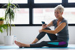 canvas print picture Senior active woman using smart phone at home after practicing yoga. The use of technology by the elderly.