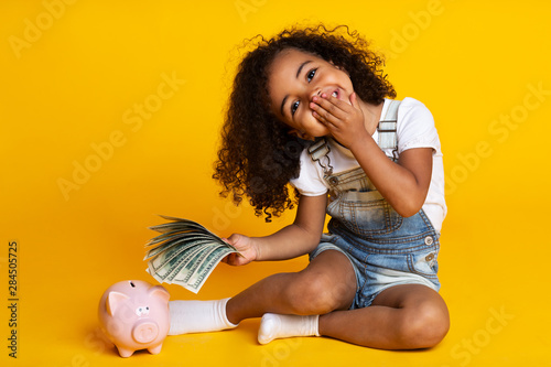 Valokuvatapetti Cute little girl with piggy bank and banknotes, yellow background