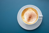 cup of cappuccino with cocoa powder on a blue background, view directly from above, copy space
