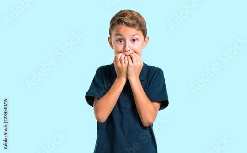 Fototapeta  Little boy is a little bit nervous and scared on blue background