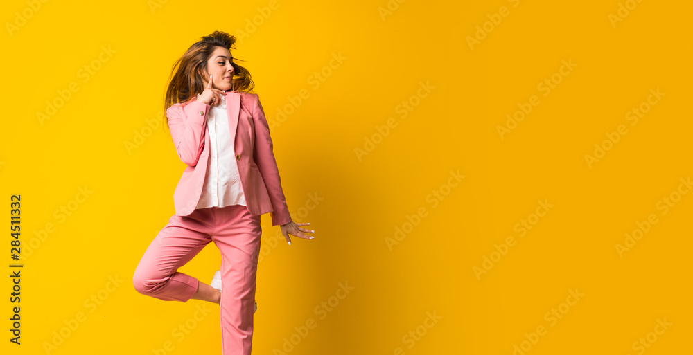 Fototapety, obrazy: Young woman jumping over isolated yellow wall