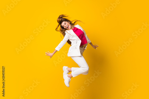 Vászonkép Young woman jumping over isolated yellow wall
