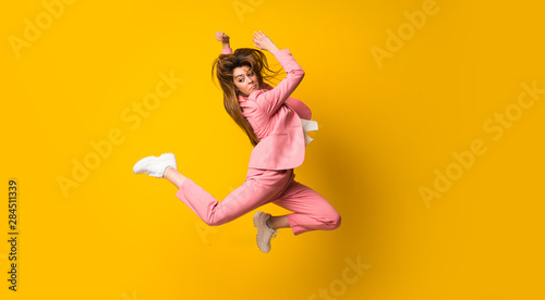 Obraz Young woman jumping over isolated yellow wall - fototapety do salonu