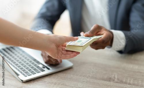Fototapeta Bank manager holding stack of cash giving credit to customer obraz