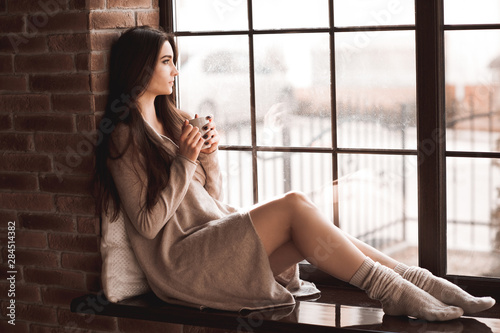 Beautiful young woman holding cup of tea sitting on windowsill in room. Wearing knitted sweater and socks. Winter season.