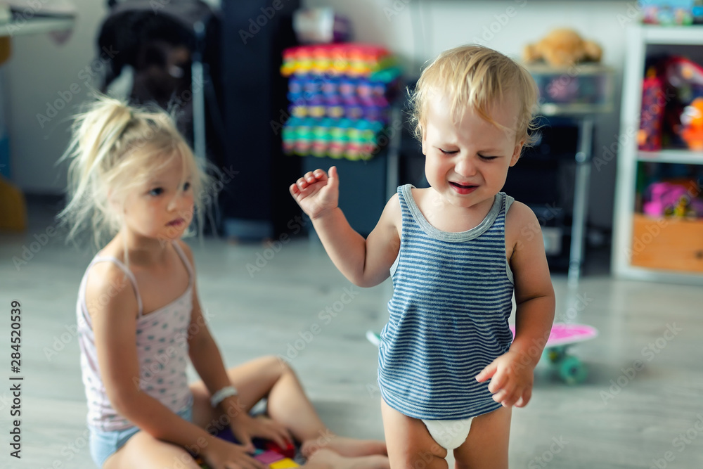 Fototapety, obrazy: Two little siblings children quarrelling after playing at room at house. Crying offended toddler boy arguing with elder sister. Family rivalry and generation conflict concept