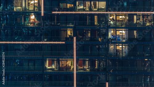 Fototapeta Lights in windows of modern multiple story building in urban setting at night timelapse obraz na płótnie