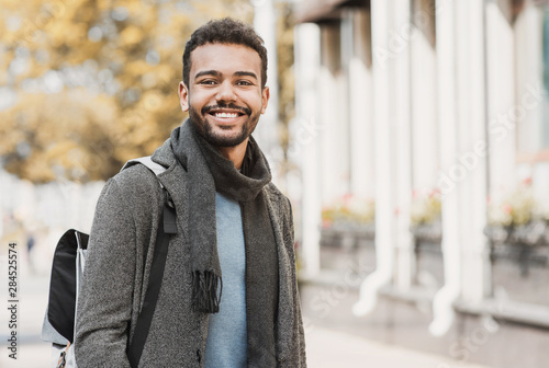 fototapeta na lodówkę Handsome joyful man autumn portrait. Smiling men student wearing warm clothes in a city in winter
