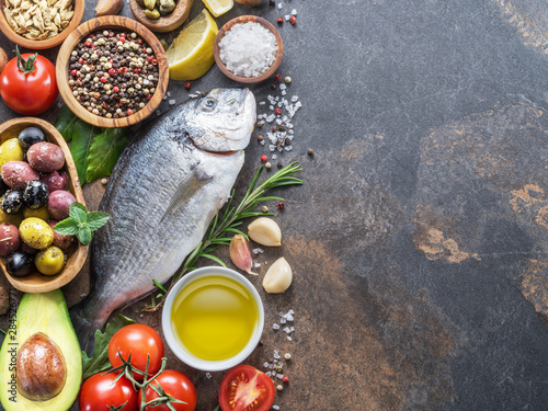 Fototapeta  Raw dorado fish with spices and vegetables on the graphite board.