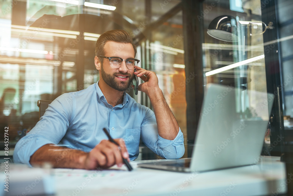 Fototapety, obrazy: Customer support. Portrait of young and cheerful businessman in eyeglasses and formal wear talking on the phone and smiling while sitting in the office