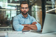 Leinwanddruck Bild - Confidence. Young bearded businessman in eyeglasses and formal wear looking at camera and keeping arms crossed while sitting in modern office