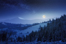 Wonderful Winter Night Scenery In Mountains.  Snow Covered Forested Hills. Full Moon On A Starry Sky Above The Distant Ridge.