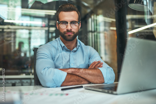 Confidence. Young bearded businessman in eyeglasses and formal wear looking at camera and keeping arms crossed while sitting in modern office