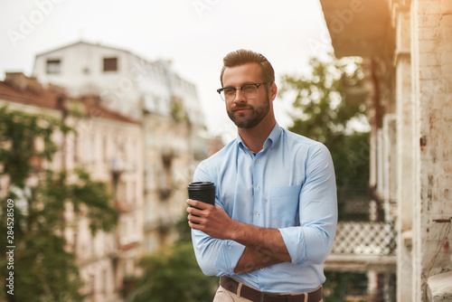 Obraz Relaxing after work. Young and handsome bearded man in eyeglasses and formal wear holding cup of coffee and looking away while standing at the office balcony - fototapety do salonu