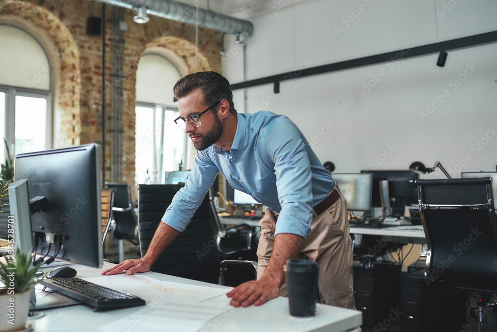 Fototapety, obrazy: Busy day. Young bearded businessman in eyeglasses and formal wear using computer while standing in the modern office