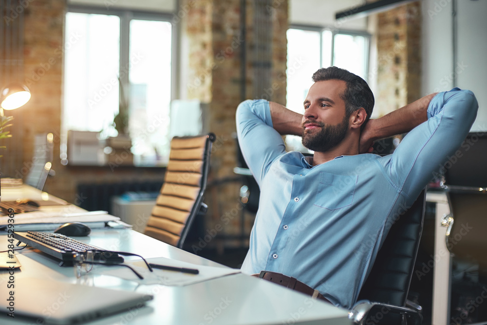 Fototapety, obrazy: Work done. Satisfied young bearded businessman leaning back with hands behind head and relaxing while sitting in the modern office