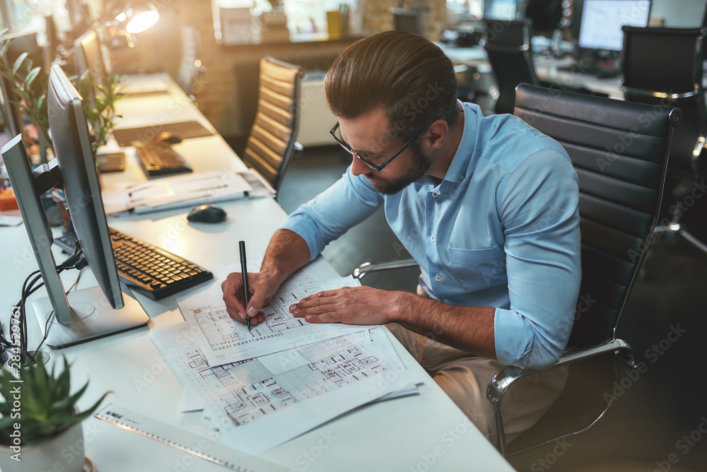 Fototapeta Architectural project. Successful busy bearded man in eyeglasses and formal wear drawing something while working in the office