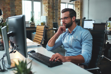 New project. Side view of young bearded man in eyeglasses and formal wear working on computer and touching his chin while sitting in the modern office