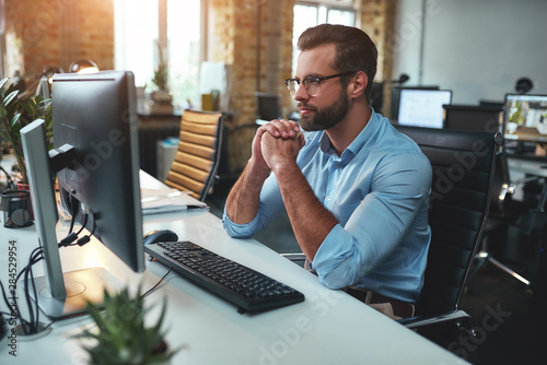 Thinking. Side view of young bearded man in eyeglasses and formal wear working on computer and keeping palms pressed together while sitting in the modern office