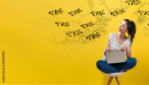 Fototapeta Tax problem theme with young woman using a laptop computer obraz