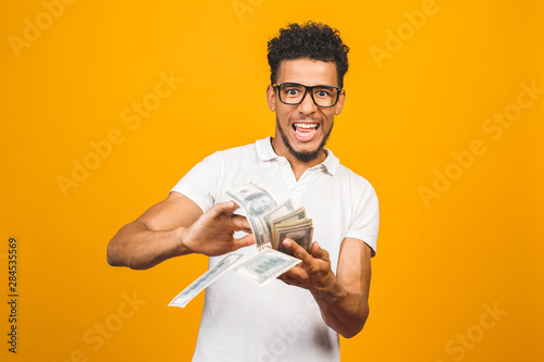 Fotografía Portrait of a happy young afro american man throwing out money banknotes isolated over yellow background