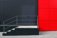 Emergency Exit Of The Modern Industry Building. Black Wall, Black Door, Red Wall And Staircase With Railing.