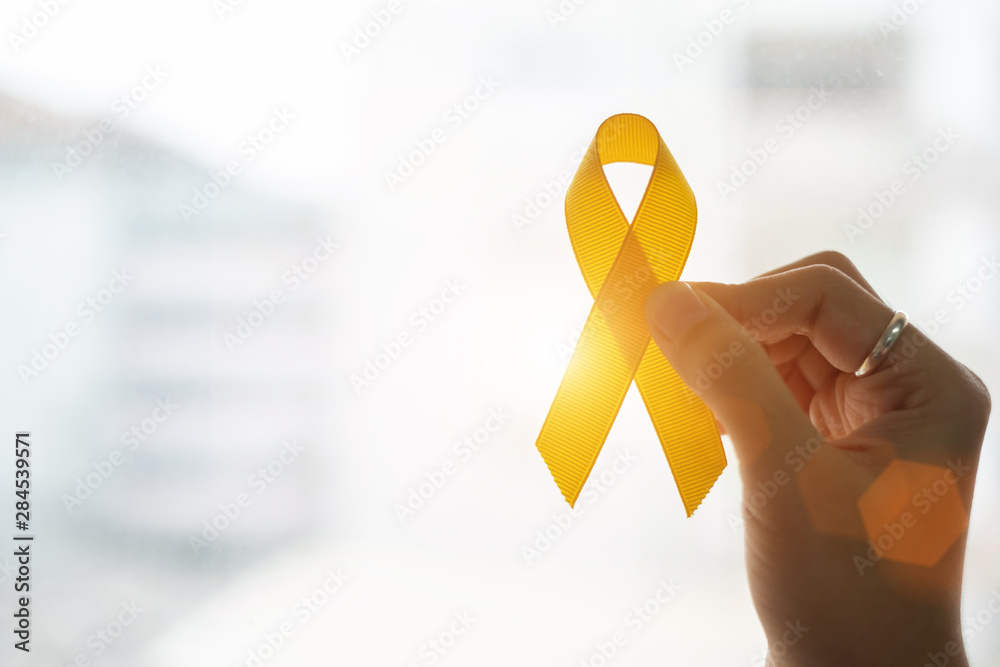 Fototapeta Suicide prevention and Childhood Cancer Awareness, Yellow Ribbon on wooden background  for supporting people living and illness. children Healthcare and World cancer day concept