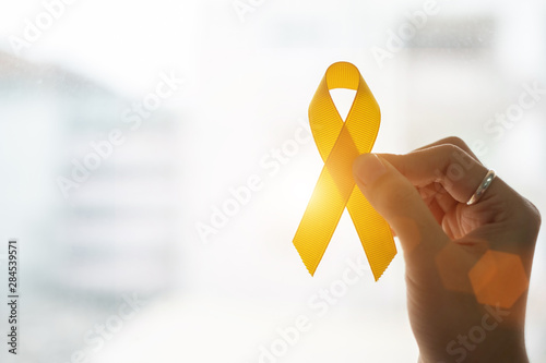 Obraz na plátně Suicide prevention and Childhood Cancer Awareness, Yellow Ribbon on wooden background  for supporting people living and illness