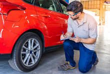 Technician With Safety Glasses Checking The Tires Of A Car During A Vehicle Inspection