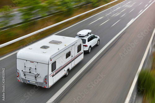travel on car with caravan trailer by highway Canvas