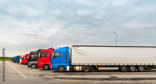 fototapeta na szkło Trucks on parking, cargo transportation in Europe