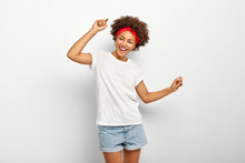 Carefree Pleased Teenage Girl Has Fun, Dances Joyfully With Raised Arms, Being Entertained And Amused, Wears Summer Clothes, Laughs Happily, Enjoys Cool Music, Isolated On White Wall, Being On Party