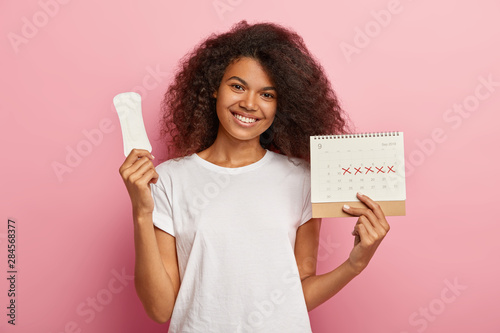 Portrait of good looking feminine girl has Afro hairstyle, holds monthly calendar, clean sanitary napkin, has menstrual cycle, happy to have good women health Canvas Print
