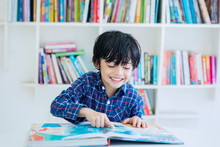 Happy Little Boy Reading A Book In The Library